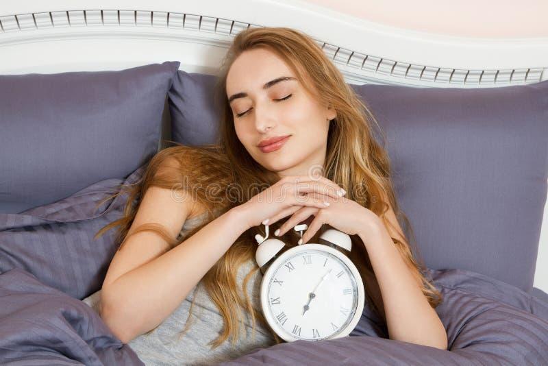 Έννοια της εργασίας overslept, κακή αϋπνία ύπνου - το νέο όμορφο νυσταλέο κορίτσι με ιδιαίτερες προσοχές κρατά ένα ρολόι και βρίσ στοκ εικόνα