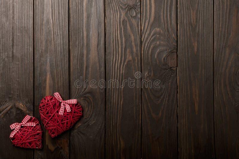 Έννοια της ημέρας βαλεντίνων ` s Ψάθινες καρδιές στο σκοτεινό ξύλινο backgro στοκ εικόνες
