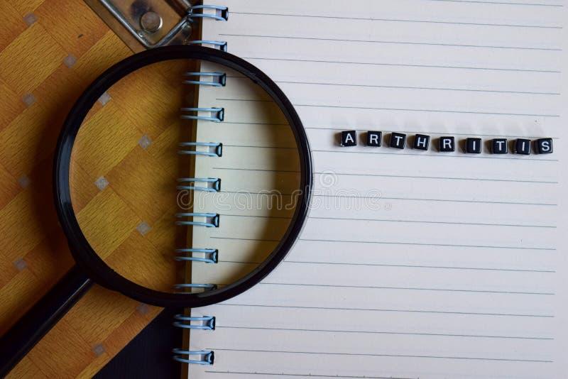 Έννοια της λέξης αρθρίτιδας στους ξύλινους κύβους, στην ενίσχυση - γυαλί, τα βιβλία στο υπόβαθρο στοκ φωτογραφίες με δικαίωμα ελεύθερης χρήσης