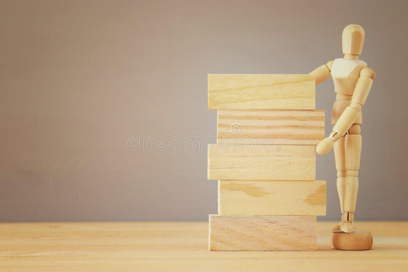 Έννοια της οικοδόμησης της επιτυχίας Ξύλινη πλαστή στάση δίπλα στους κενούς φραγμούς στοκ φωτογραφία με δικαίωμα ελεύθερης χρήσης