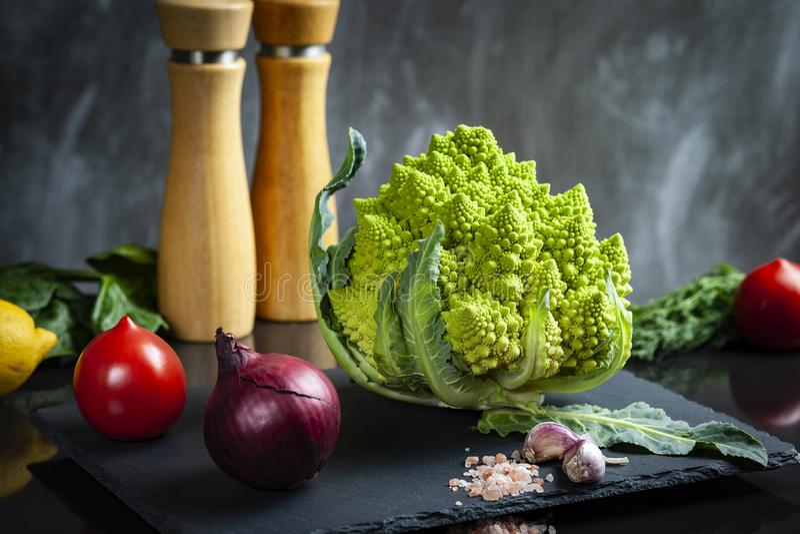 Έννοια της οργανικής τροφής με τα φρέσκα λαχανικά: Μπρόκολο Romanesco, ώριμες ντομάτες, κόκκινο κρεμμύδι στοκ εικόνες