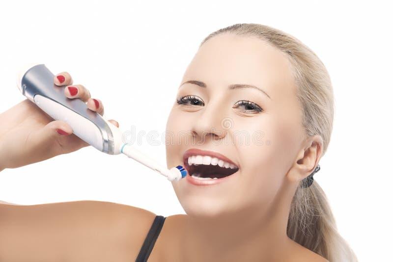 Έννοια της οδοντικής υγείας: Ξανθή καυκάσια γυναίκα που βουρτσίζει το γράμμα Τ της στοκ φωτογραφία