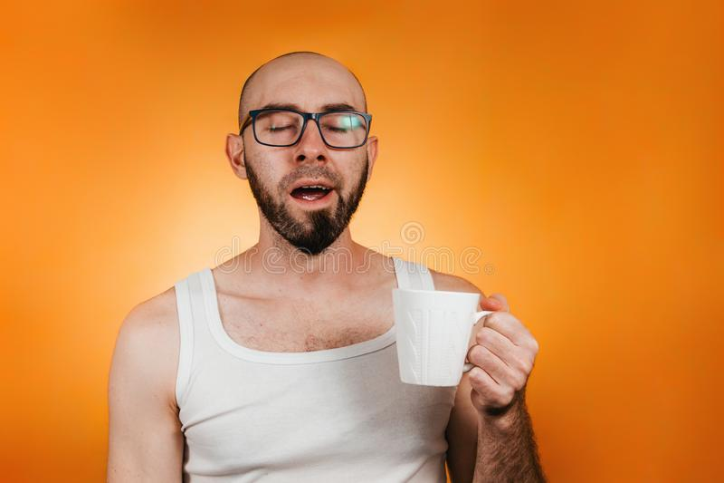 Έννοια της πρωινής αφύπνισης και της παραγωγικότητας Ένας φαλακρός, γενειοφόρος άντρας με γυαλιά, κρατώντας μια κούπα καφέ ή τσάι στοκ φωτογραφία με δικαίωμα ελεύθερης χρήσης