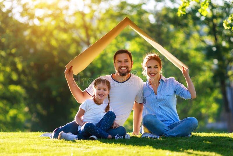 Έννοια της υποθήκης και της κατοικίας για τις οικογένειες πατέρας και παιδί μητέρων από τη στέγη του σπιτιού στη φύση στοκ φωτογραφία