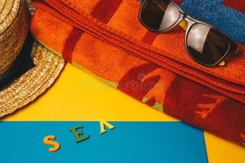 Έννοια της χαλάρωσης στην παραλία θάλασσα επιγραφής σε ένα κίτρινο υπόβαθρο με τα γυαλιά ηλίου, μια πετσέτα και ένα καπέλο αχύρου στοκ φωτογραφία