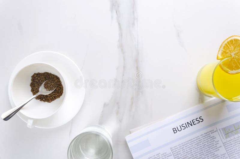 Έννοια του επιχειρησιακού πρωινού στο γραφείο Φλιτζάνι του καφέ, γυαλί του wate, χυμός από πορτοκάλι και φρέσκια εφημερίδα διάστη στοκ φωτογραφία με δικαίωμα ελεύθερης χρήσης