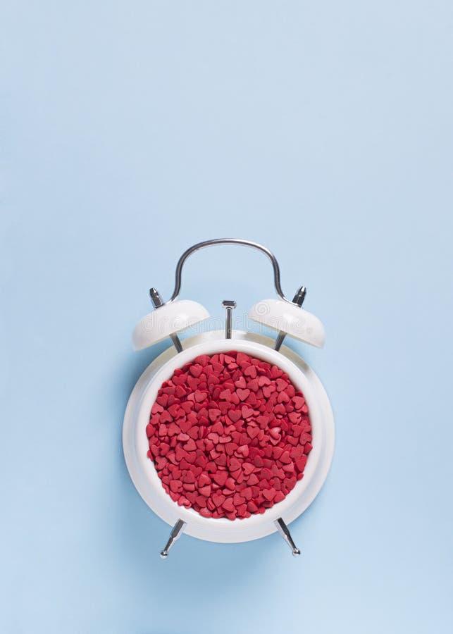 Έννοια του χρόνου γενεθλίων, βαλεντίνων και κομμάτων στην μπλε κρητιδογραφία bakground με το συναγερμό στοκ φωτογραφίες