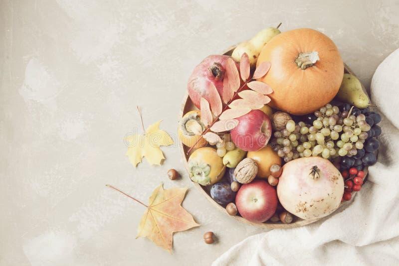 Έννοια τροφίμων φθινοπώρου Φρούτα, λαχανικά και καρύδια στον ξύλινο κύκλο στοκ εικόνες