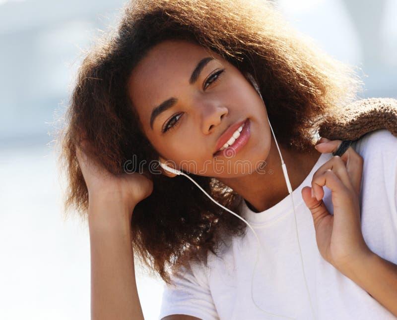 Έννοια τρόπου ζωής: Νεαρή αφρικανή αμερικανίδα με κινητό τηλέφωνο και ακουστικά, χαμογελαστή στοκ εικόνα με δικαίωμα ελεύθερης χρήσης