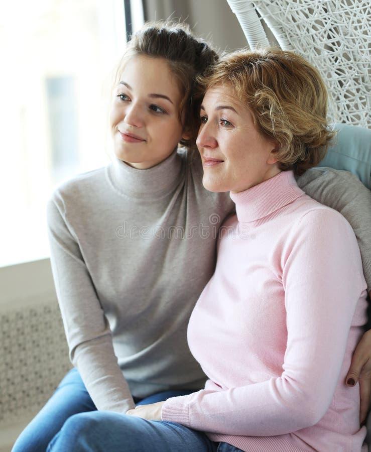 Έννοια τρόπου ζωής, οικογενειών και ανθρώπων: Ευτυχής νέα γυναίκα και η μητέρα της στο σπίτι, ευτυχής οικογένεια στοκ εικόνα