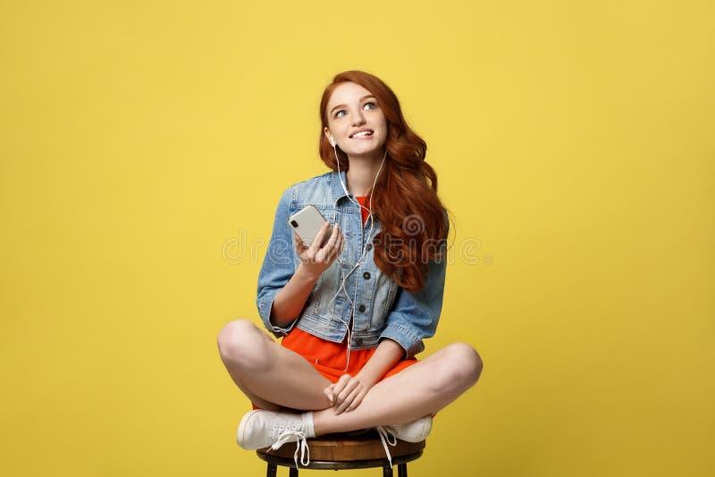 Έννοια τρόπου ζωής: Το όμορφο κορίτσι με τη μακριά σγουρή κόκκινη τρίχα απολαμβάνει τη μουσική στο τηλέφωνό της και σε ξύλινο στοκ εικόνες