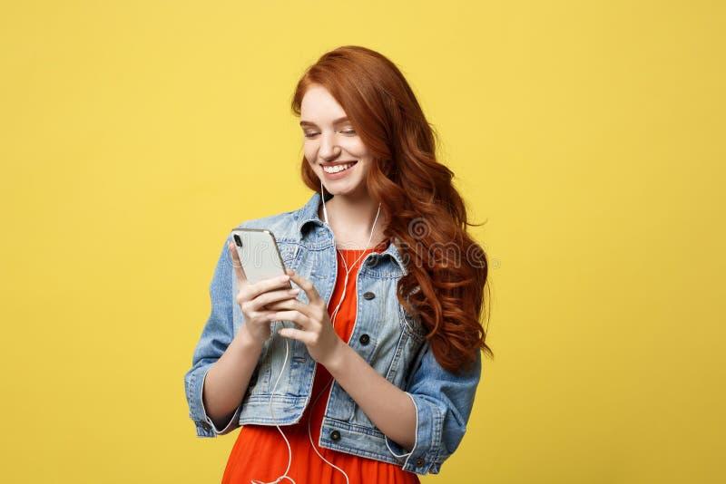 Έννοια τρόπου ζωής: Όμορφη νέα γυναίκα στα ακουστικά που ακούει τη μουσική στο ανοικτό κίτρινο υπόβαθρο στοκ εικόνες
