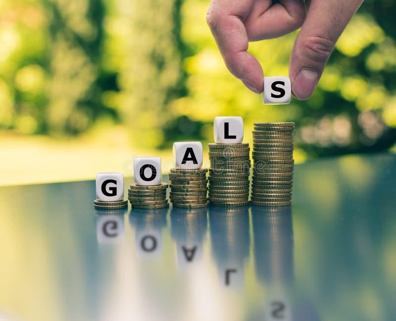 Έννοια των οικονομικών στόχων Χωρίστε σε τετράγωνα τοποθετημένος στους αυξανόμενους υψηλούς σωρούς της μορφής νομισμάτων τη λέξη  στοκ εικόνες με δικαίωμα ελεύθερης χρήσης