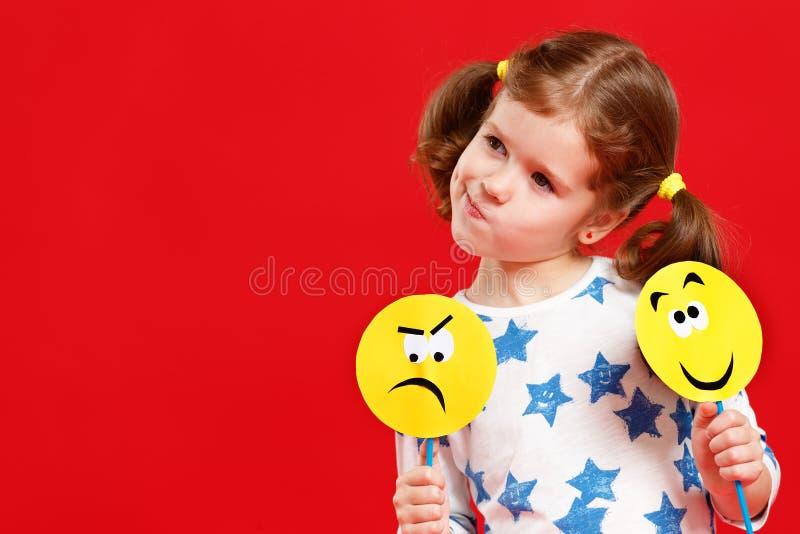 Έννοια των συγκινήσεων παιδιών ` s το κορίτσι παιδιών επιλέγει μεταξύ ενός λυπημένου στοκ φωτογραφία με δικαίωμα ελεύθερης χρήσης
