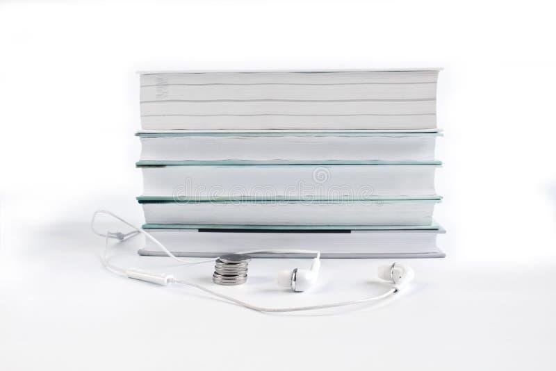 Έννοια των φτηνών ακουστικών βιβλίων Άσπρα ακουστικά και νομίσματα κοντά στο σωρό των βιβλίων r στοκ φωτογραφία