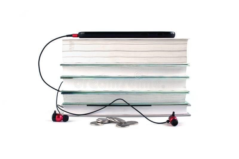 Έννοια των φτηνών ακουστικών βιβλίων Κόκκινα ακουστικά και κινητός στο σωρό των βιβλίων Άσπρο υπόβαθρο με το διάστημα για το κείμ στοκ φωτογραφίες