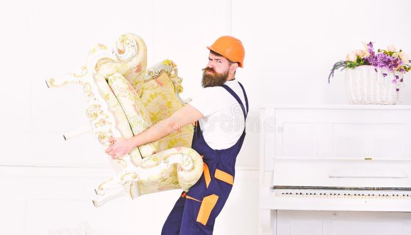 Έννοια υπηρεσιών παράδοσης Το άτομο με τη γενειάδα, τον εργαζόμενο στις φόρμες και το κράνος ανυψώνει επάνω την πολυθρόνα, άσπρο  στοκ εικόνα