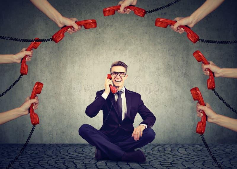 Έννοια υποστήριξης πελατών επιχειρησιακών επικοινωνιών Επιχειρηματίας πάντα στο τηλέφωνο που απαντά σε πολλά τηλεφωνήματα στοκ φωτογραφία