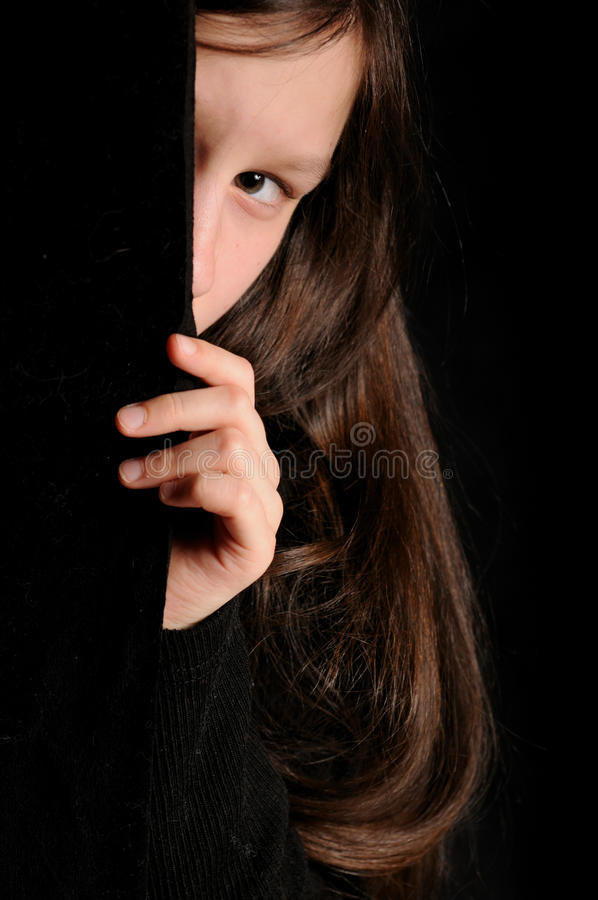 Έννοια φόβου Κορίτσι που κοιτάζει έξω στο μαύρο υπόβαθρο στοκ εικόνες