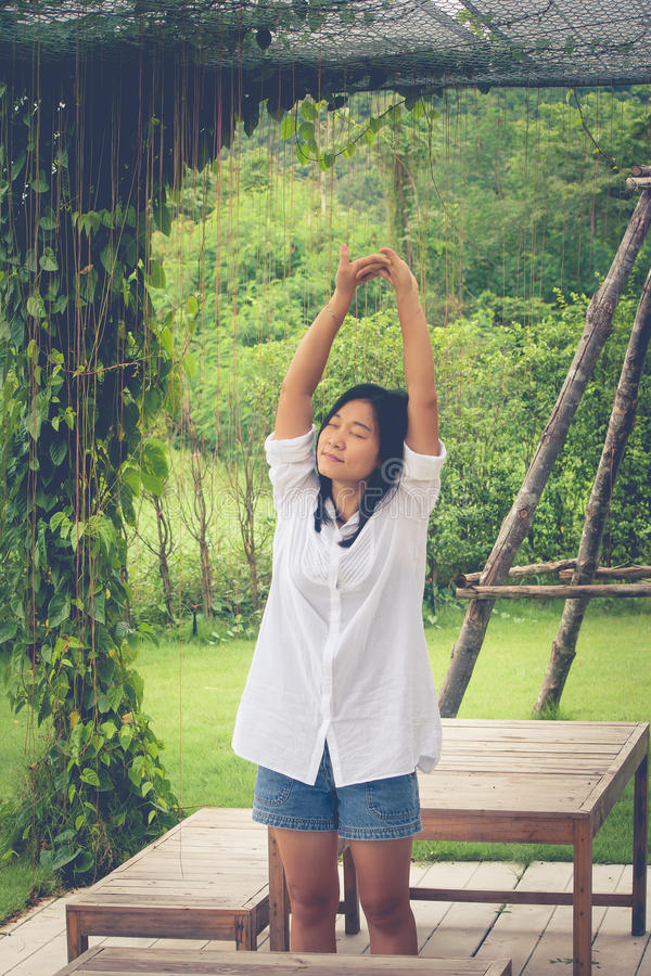 Έννοια χαλάρωσης: Ασιατικά πουκάμισο και τέντωμα ένδυσης γυναικών άσπρα στον κήπο στοκ φωτογραφίες με δικαίωμα ελεύθερης χρήσης