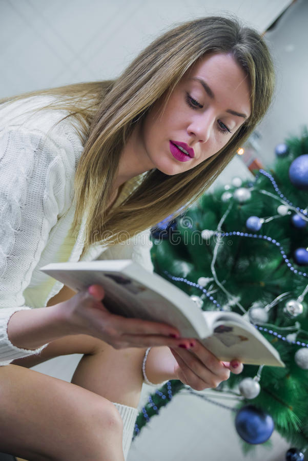 Έννοια Χριστουγέννων, διακοπών και ανθρώπων - ευτυχές νέο βιβλίο ανάγνωσης γυναικών στο σπίτι Ευτυχής όμορφη προκλητική γυναίκα μ στοκ εικόνες