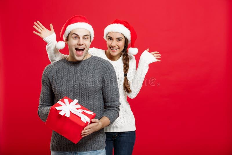 Έννοια Χριστουγέννων - νέα γυναίκα που καλύπτει τα μάτια ανδρών ` s με το χέρι και που δίνει στην έκπληξη το μεγάλο δώρο Απομονωμ στοκ εικόνα