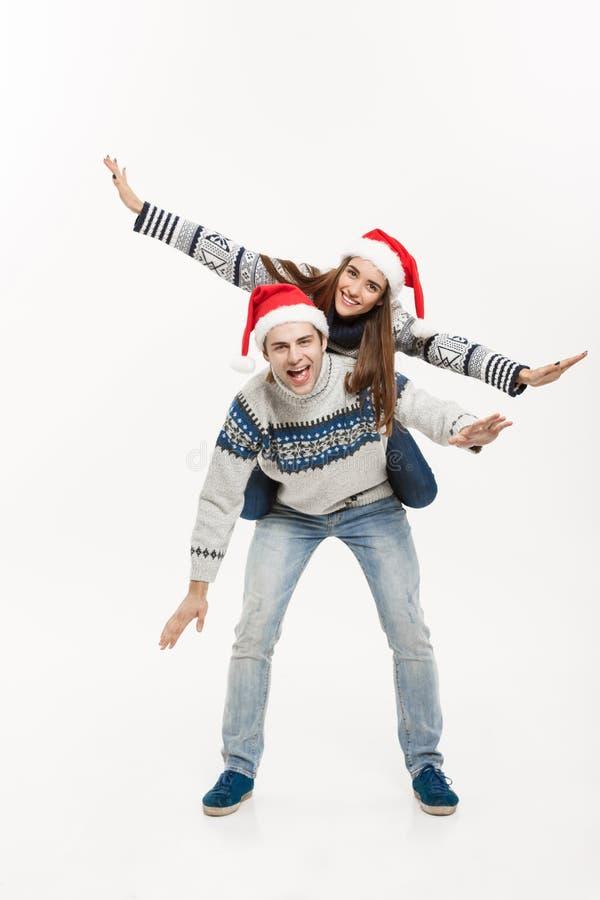 Έννοια Χριστουγέννων - ολόκληρο νέο ευτυχές ζεύγος στα πουλόβερ που απολαμβάνει piggyback το γύρο που απομονώνεται στο άσπρο γκρί στοκ εικόνες