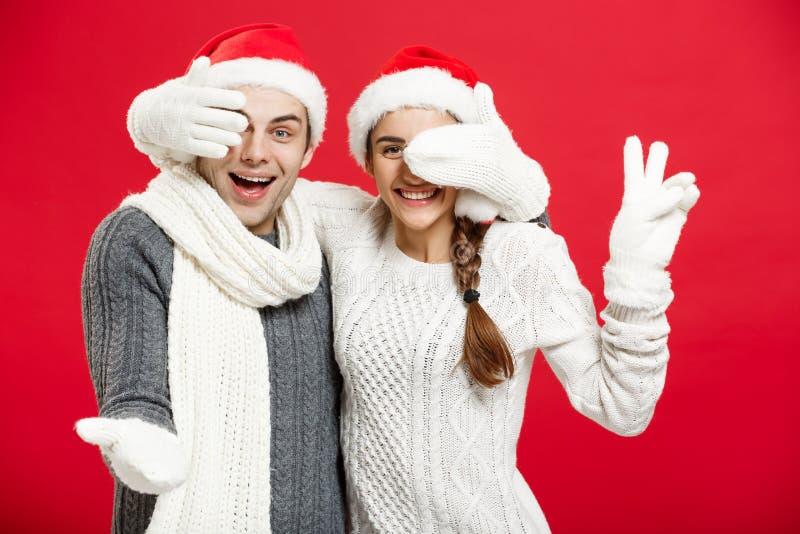 Έννοια Χριστουγέννων - το νέο ευτυχές μοντέρνο ζεύγος στα χειμερινά ενδύματα κλείνει τα μάτια κάθε άλλα που γιορτάζουν στη ημέρα  στοκ εικόνα