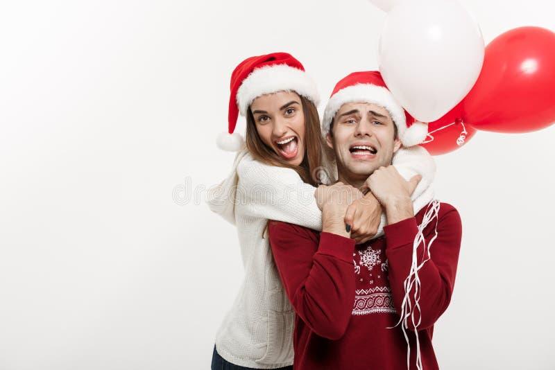 Έννοια Χριστουγέννων - το νέο μπαλόνι εκμετάλλευσης φίλων αγκαλιάζει και παίζει με το φίλο της που κάνει μια έκπληξη επάνω στοκ φωτογραφία με δικαίωμα ελεύθερης χρήσης