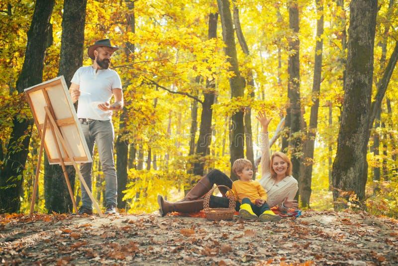 Έννοια χόμπι Καλλιτέχνης ζωγράφων με την οικογενειακή χαλάρωση στη δασική ζωγραφική στη φύση Νέα εικόνα έναρξης i στοκ εικόνα