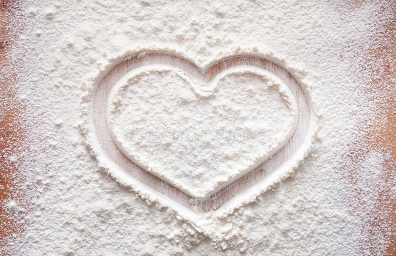 Έννοια ψησίματος στο ξύλινο υπόβαθρο, ψεκασμένο αλεύρι με την καρδιά, διάστημα αντιγράφων στοκ εικόνες