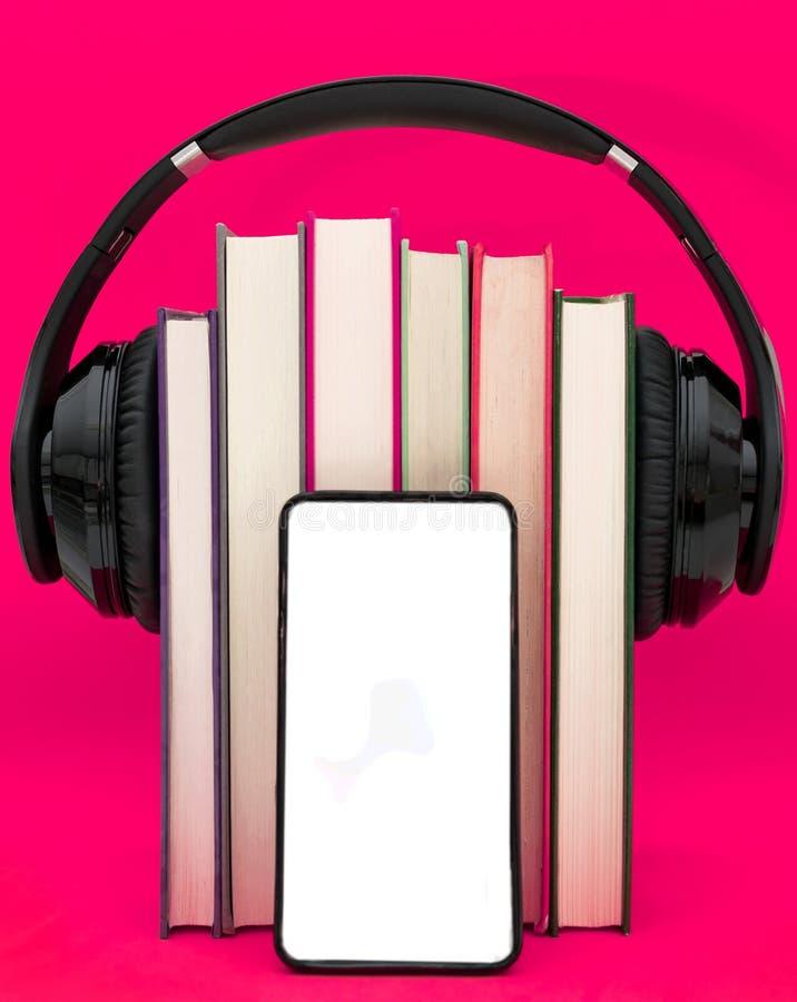 Έννοια Audiobooks Ακουστικά που τίθενται πέρα από το βιβλίο στο ρόδινο πορφυρό υπόβαθρο Έξυπνο τηλέφωνο στοκ φωτογραφίες με δικαίωμα ελεύθερης χρήσης