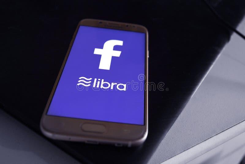 Έννοια Cryptocurrency Libra Facebook με το κινητό τηλέφωνο με το λογότυπο Libra και Facebook στην κινητή τηλεφωνική οθόνη bue στοκ φωτογραφίες