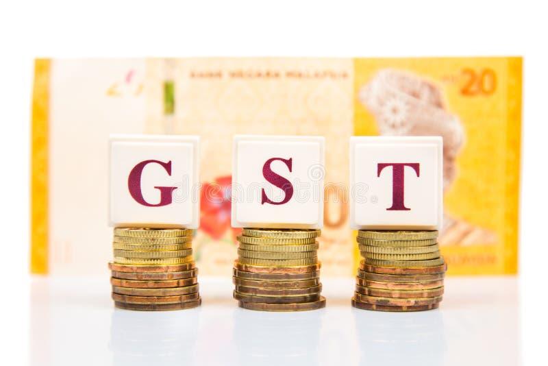 Έννοια GST ή αγαθού και φόρου υπηρεσιών με το σωρό του νομίσματος και του νομίσματος RINGGIT της Μαλαισίας στοκ φωτογραφία