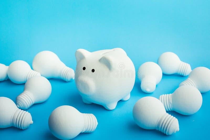 Έννοιες ιδεών χρημάτων αποταμίευσης με τη piggy τράπεζα και lightbulb στο μπλε χρώμα στοκ εικόνες με δικαίωμα ελεύθερης χρήσης