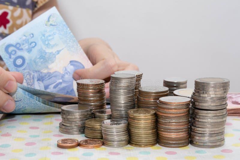 Έννοιες λογιστικής παρούσες από τους θηλυκούς λογαριασμούς μπατ χεριών μετρώντας πίσω από τους σωρούς νομισμάτων χρημάτων στο λευ στοκ εικόνες