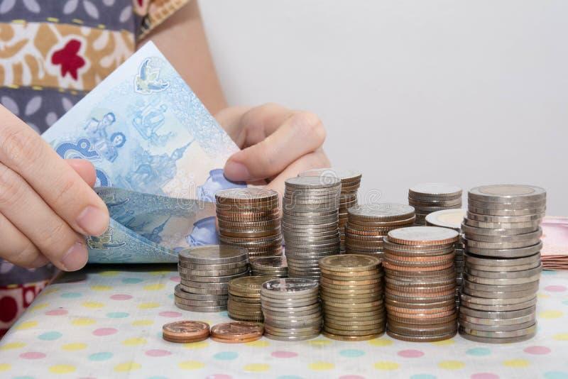 Έννοιες λογιστικής παρούσες από τους θηλυκούς λογαριασμούς μπατ χεριών μετρώντας πίσω από τους σωρούς νομισμάτων χρημάτων στο λευ στοκ φωτογραφία με δικαίωμα ελεύθερης χρήσης