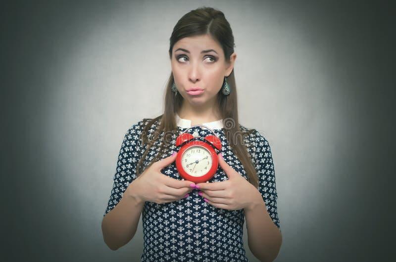 Ένοχη γυναίκα με το κόκκινο ξυπνητήρι αργά για την εργασία ή το σχολικό μάθημα oversleep αργοπορημένος στοκ φωτογραφίες