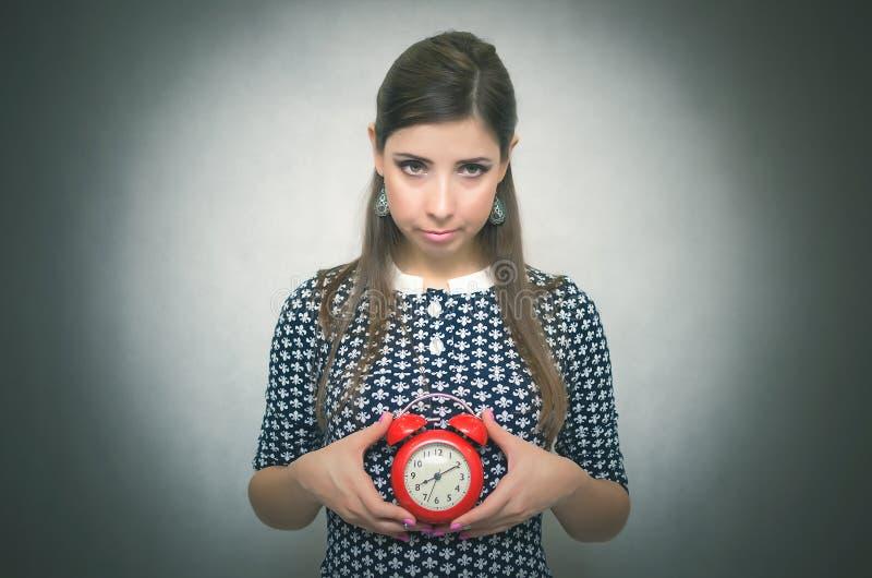 Ένοχη γυναίκα με το κόκκινο ξυπνητήρι αργά για την εργασία ή το σχολικό μάθημα oversleep αργοπορημένος στοκ εικόνα με δικαίωμα ελεύθερης χρήσης