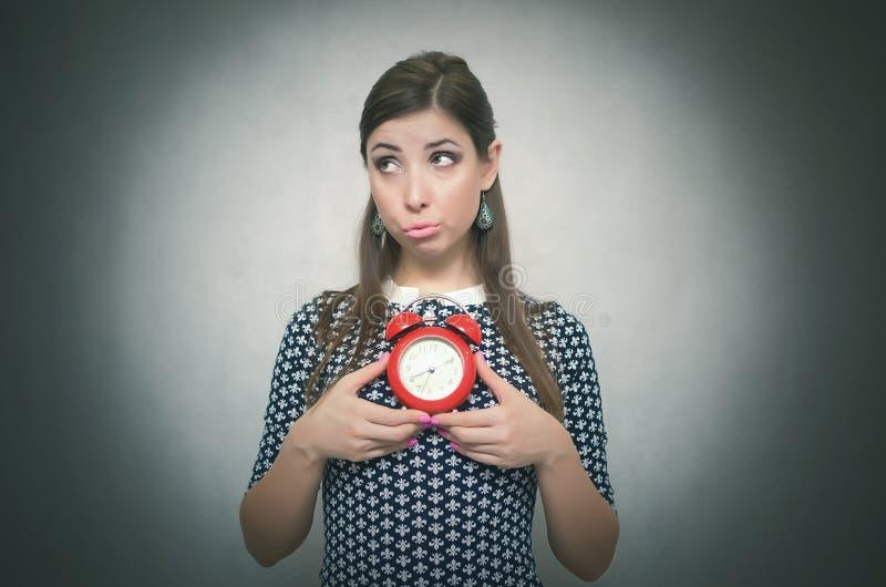 Ένοχος που λείπουν στη γυναίκα εργασίας με το κόκκινο ξυπνητήρι oversleep αργοπορημένος στοκ εικόνες