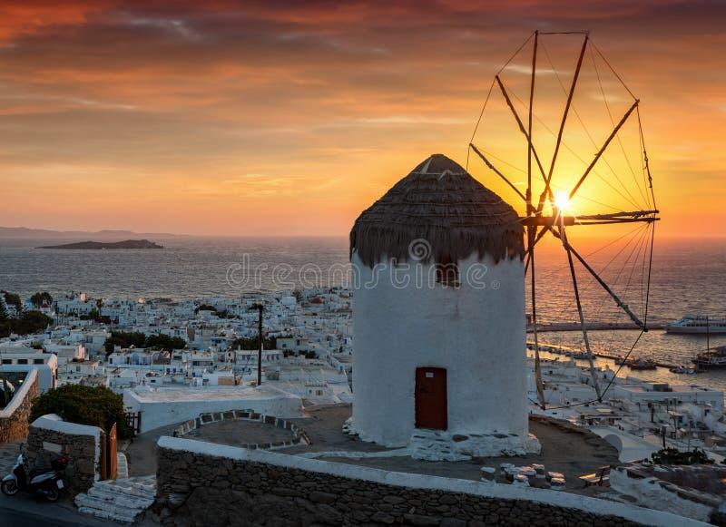 Έντονο ηλιοβασίλεμα πίσω από το διάσημο ανεμόμυλο και την πόλη του νησιού της Μυκόνου στοκ φωτογραφία