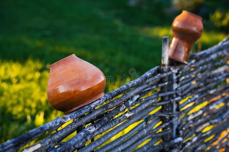 Ένωση δοχείων και κανατών αργίλου σε έναν ψάθινο ξύλινο φράκτη στοκ εικόνες με δικαίωμα ελεύθερης χρήσης