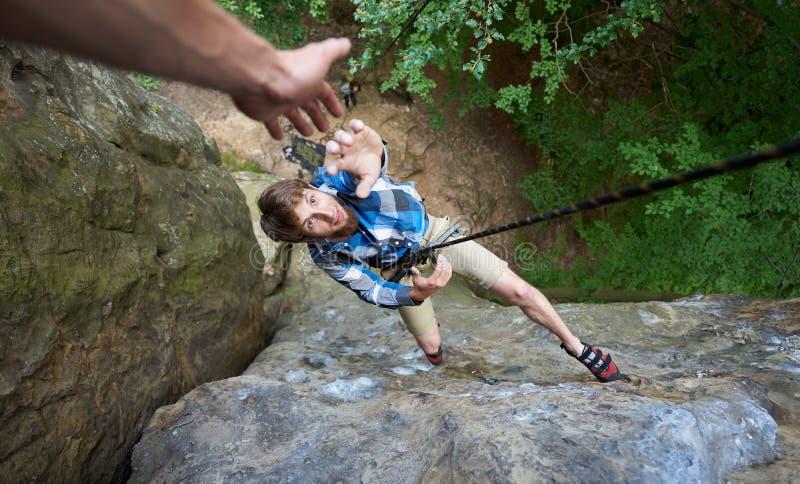 Ένωση ορειβατών στο σχοινί μεταξύ των βράχων και τέντωμα έξω του χεριού του Χέρι βοήθειας στην αναρρίχηση βράχου στοκ εικόνες