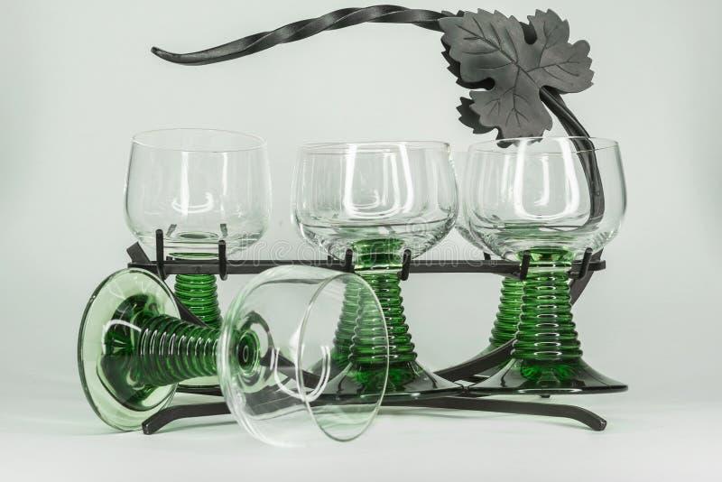 Έξι γυαλιά κρασιού με τους πράσινους μίσχους που κάθονται σε ένα ράφι επεξεργασμένου σιδήρου στοκ φωτογραφία με δικαίωμα ελεύθερης χρήσης