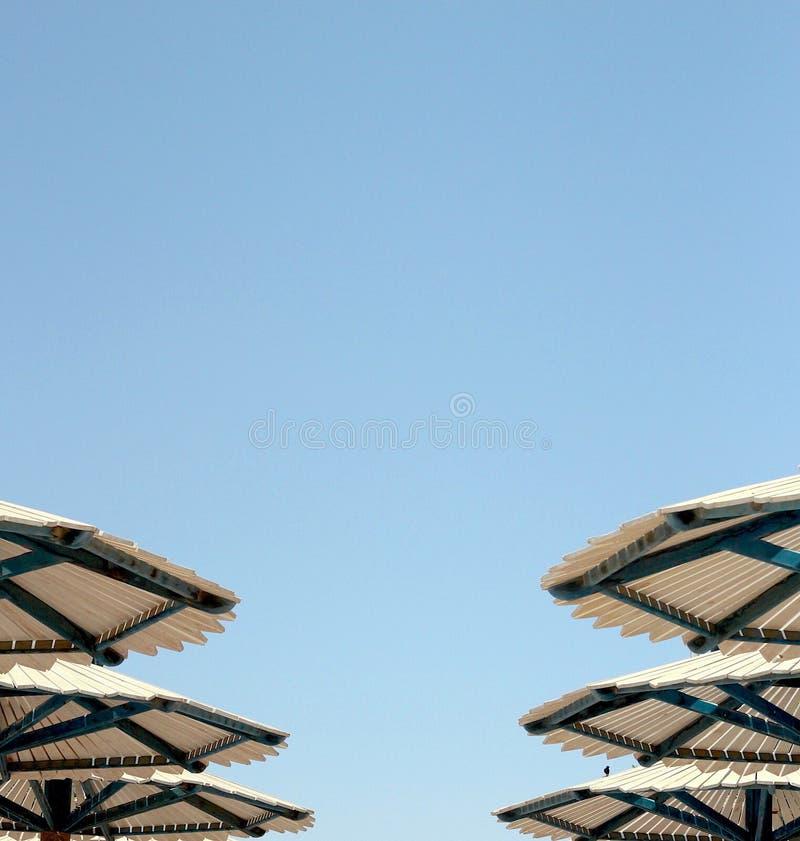 Έξι καπέλα των ομπρελών παραλιών ενάντια στο μπλε ουρανό στοκ φωτογραφίες