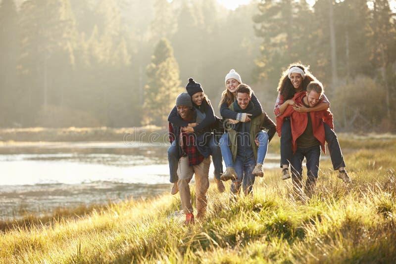 Έξι φίλοι έχουν τη διασκέδαση piggybacking στην επαρχία από τη λίμνη στοκ εικόνες