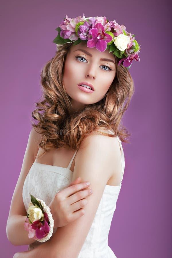 Έξοχη γυναίκα με το στεφάνι των λουλουδιών Κομψή κυρία με την σγοuρή τρίχα στοκ εικόνα με δικαίωμα ελεύθερης χρήσης