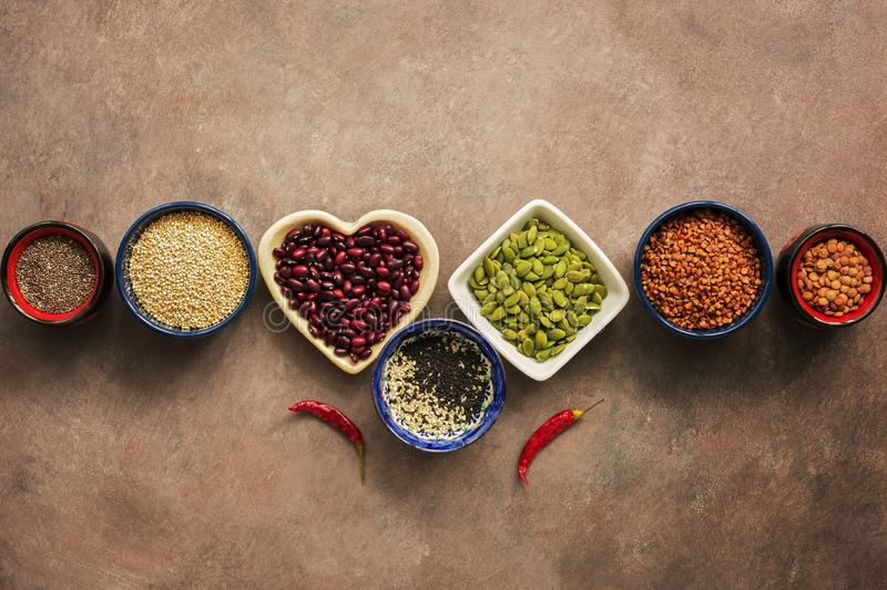 Έξοχοι δημητριακά τροφίμων, όσπρια, σπόροι και πιπέρια τσίλι σε ένα καφετί υπόβαθρο grunge Chia, quinoa, φασόλια, φαγόπυρο, φακές στοκ εικόνες