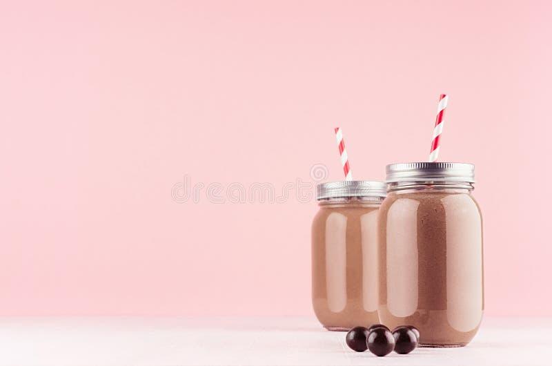Έξοχο ελαφρύ επιδόρπιο σοκολάτας γάλακτος στα βάζα με τις σφαίρες σοκολάτας, κόκκινο άχυρο, ασημένια ΚΑΠ στο σύγχρονο κομψό ρόδιν στοκ εικόνα