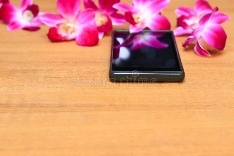 Έξυπνα λουλούδια τηλεφώνων και ορχιδεών σε ένα παλαιό ξύλινο υπόβαθρο πινάκων στοκ φωτογραφία με δικαίωμα ελεύθερης χρήσης